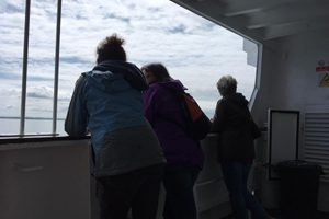 4 people on a boat looking to sea